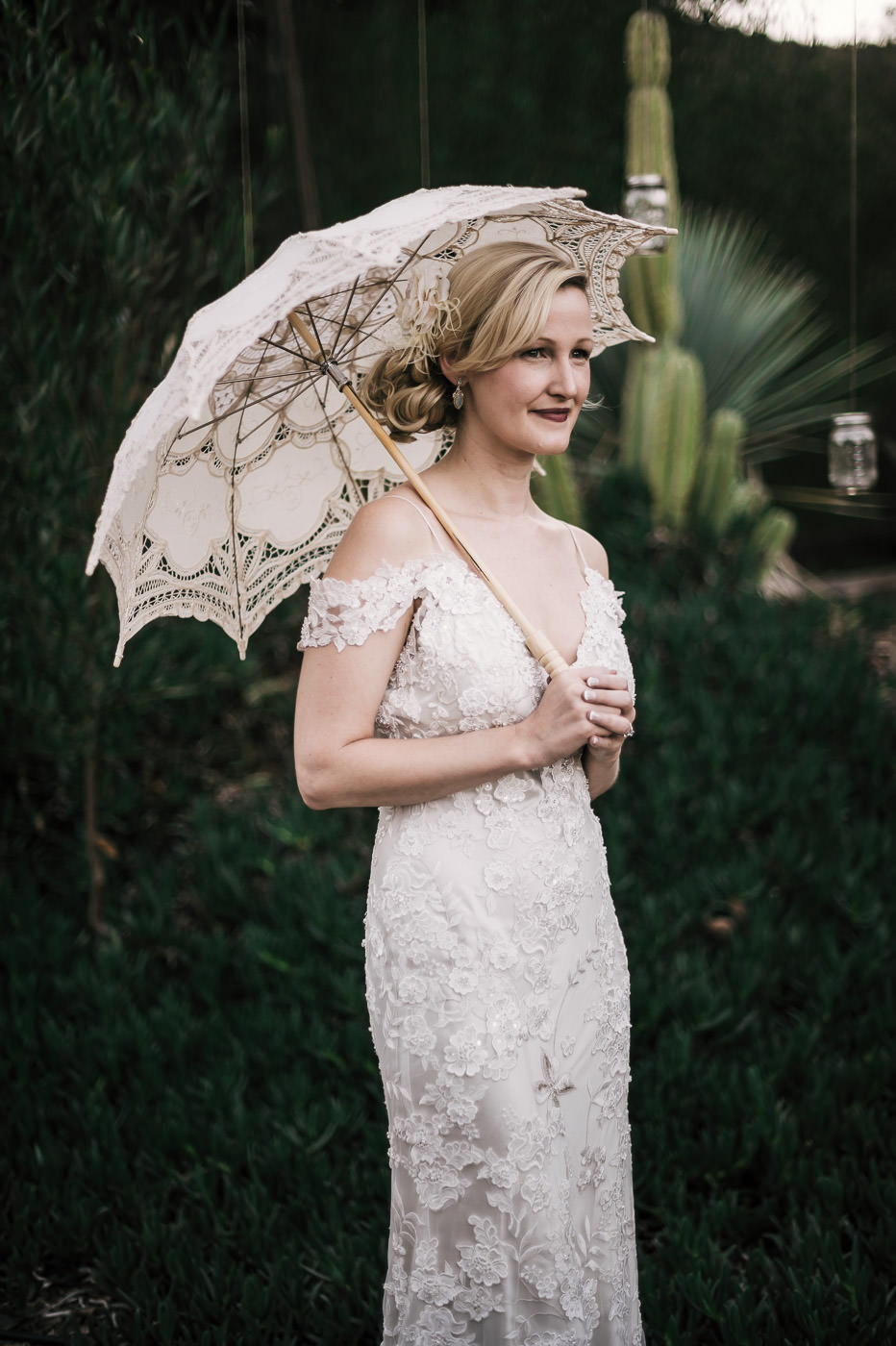 Gorgeous vintage themed bride holds a white lace parasol before her wedding at the gorgeous Whispering Oaks Terrace in Temecula California