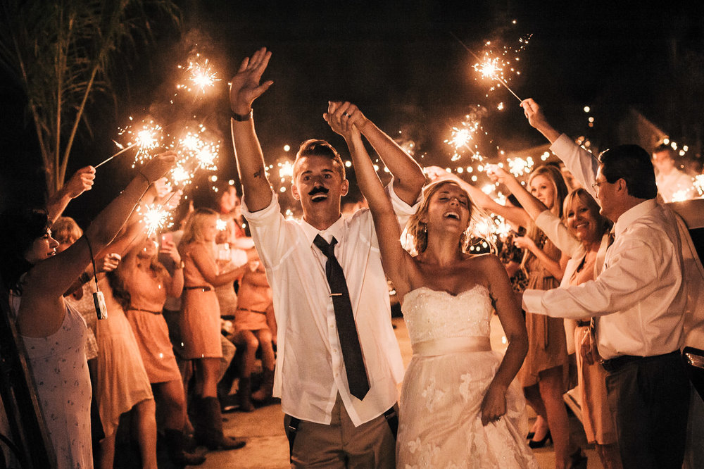 couple cheers as they make their grand exit lined by family and friends with sparklers at their vintage themed temecula wedding