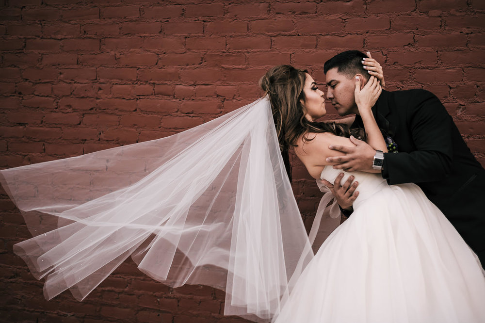 Groom dips bride romantically in front of a red brick wall as her veil blows in the wind