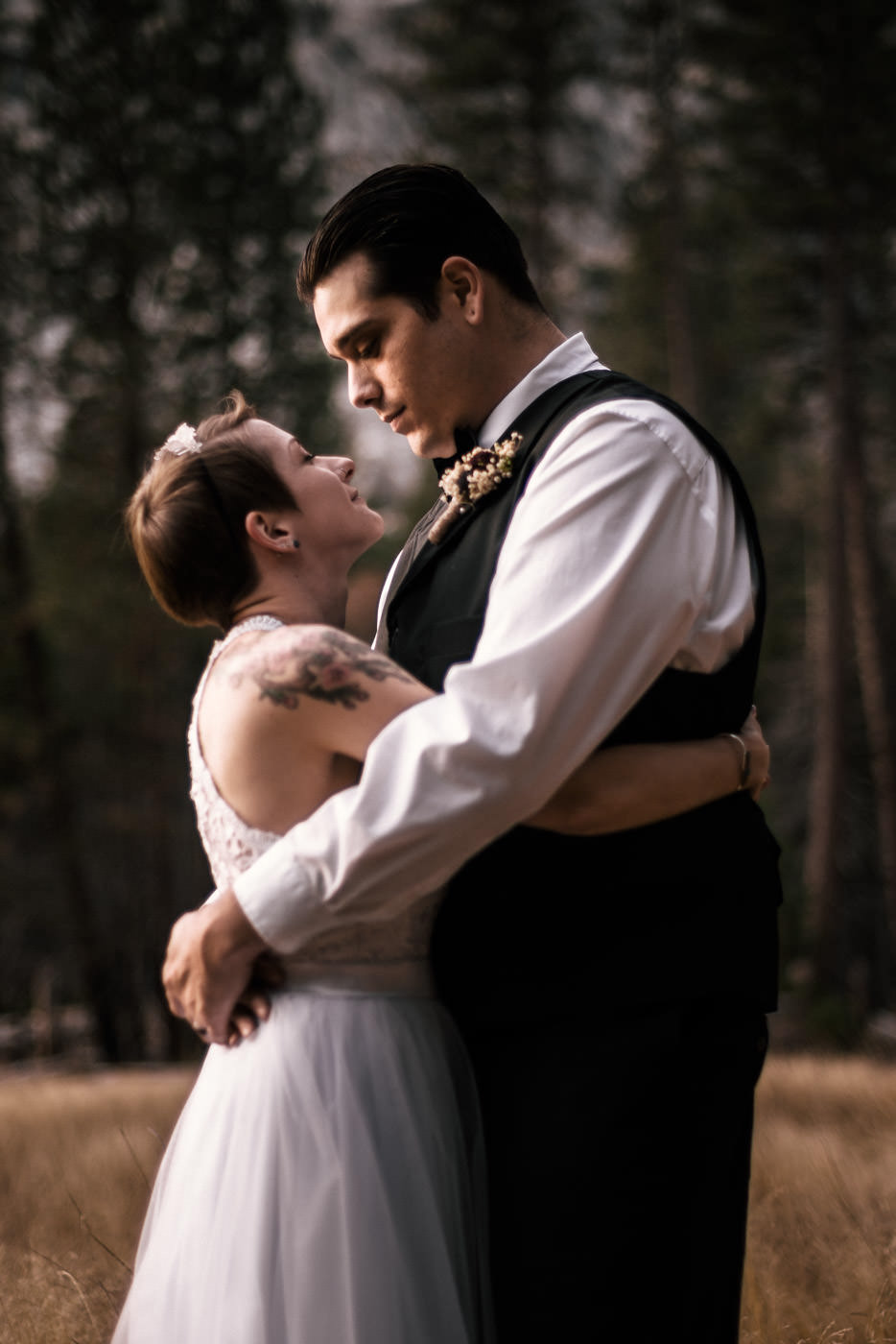 Couple holds each other romantically  in a meadow after their elopement ceremony captured by their Yosemite elopement photographer