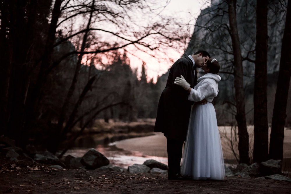 Bride and groom kiss in front of the Merced river at sunset after their elopement at Yosemite national park in December.