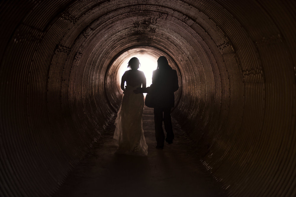 couple is sillouetted by the light at the end of the tunnel at julia pfeiffer burns state park during their intimate elopement in Big Sur