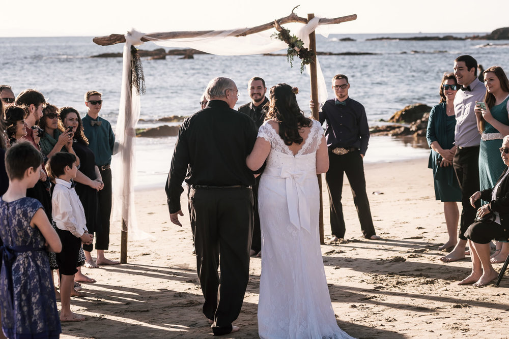 Dakota and Kirsten decided to elope to a beach closer to home. This allowed for more guests to attend their intimate elopement ceremony.  For a beautiful but simple arbor three pieces of wood were screwed together at the site decorated, and then held by two guests for the ceremony.