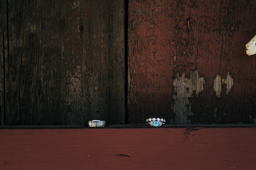 beautiful wedding ring with blue diamond sits against a rustic red wall
