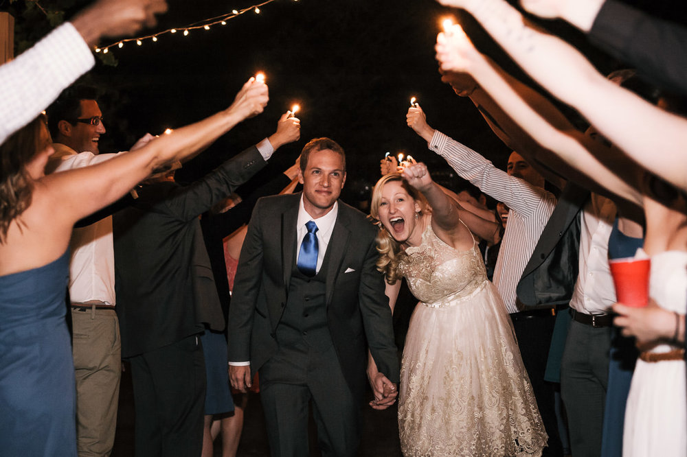 Bride and groom make their grand exit through a tunnel of their guests holding lighters on high