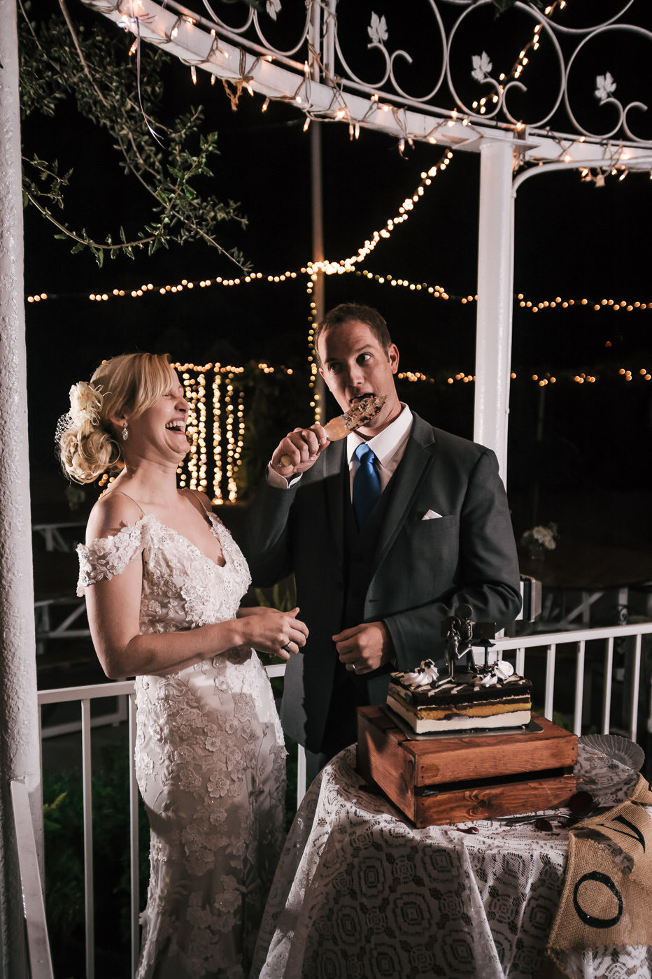 groom gets a big laugh from his bride by licking the cake cutting knife