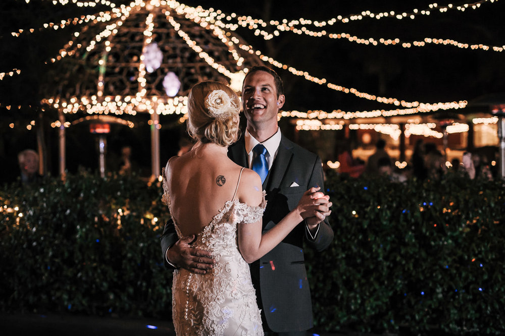 lovers share a laugh during their romantic first dance at the whispering oaks terrace