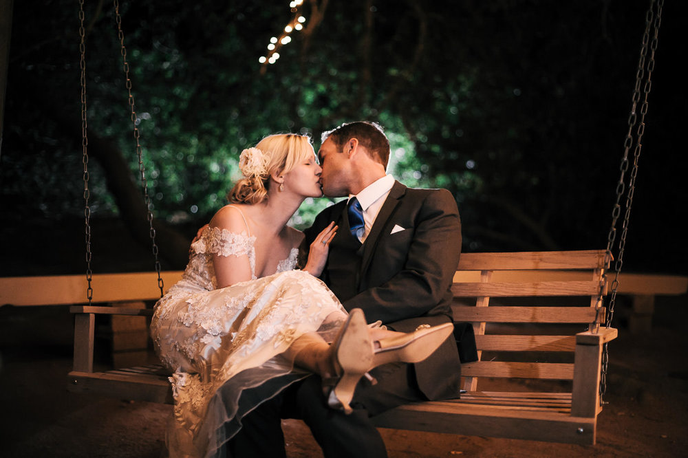 bride and groom enjoy a tender moment alone as they rock gently on a tree swing at whsipering oaks terrace