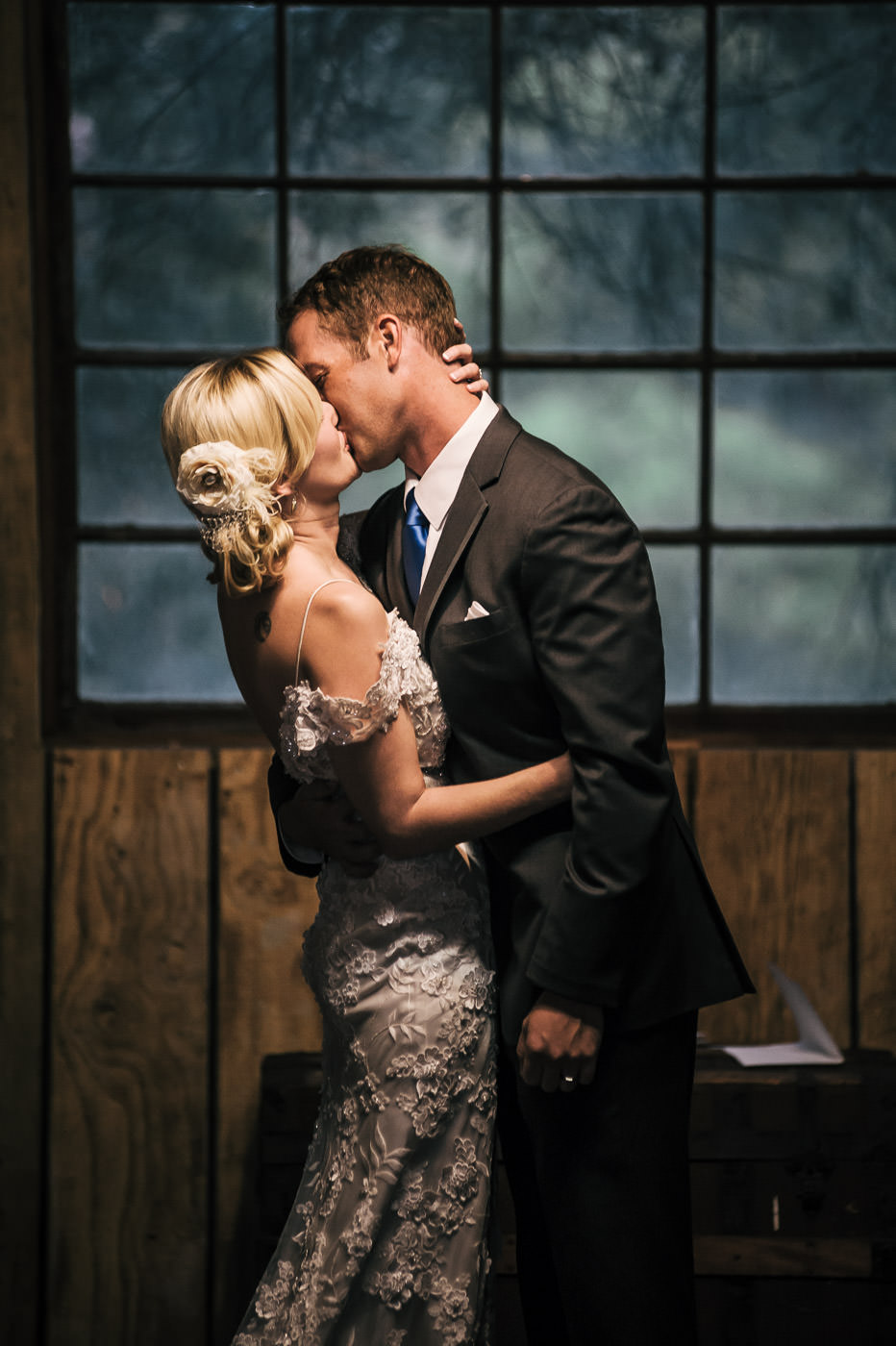 romantic first kiss between a loving bride and groom at whispering oaks terrace