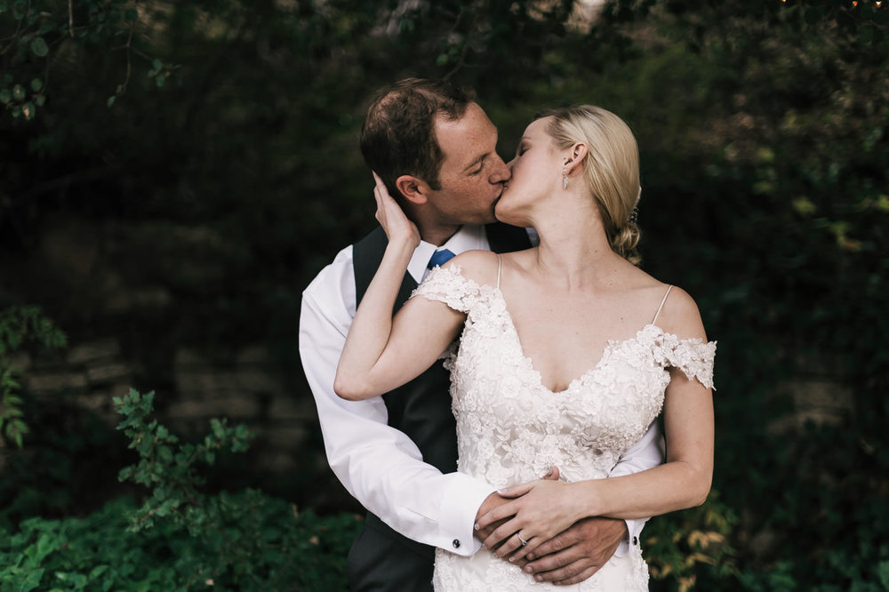 bride and groom share a romantic kiss among the oak trees in temecula californa