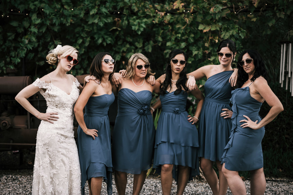 Bride and bridesmaids put on heart shapped sunglasses and strike a pose for photos at a Whispering Oaks Terrace wedding
