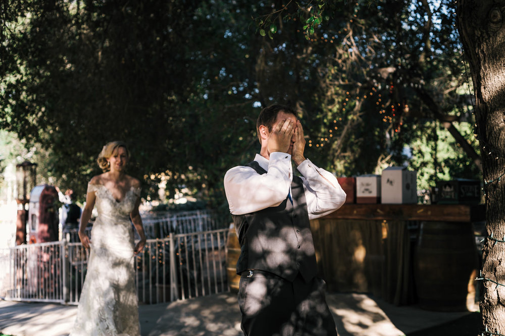 groom covers his eyes as the bride approaches for the first look at their country styled wedding.
