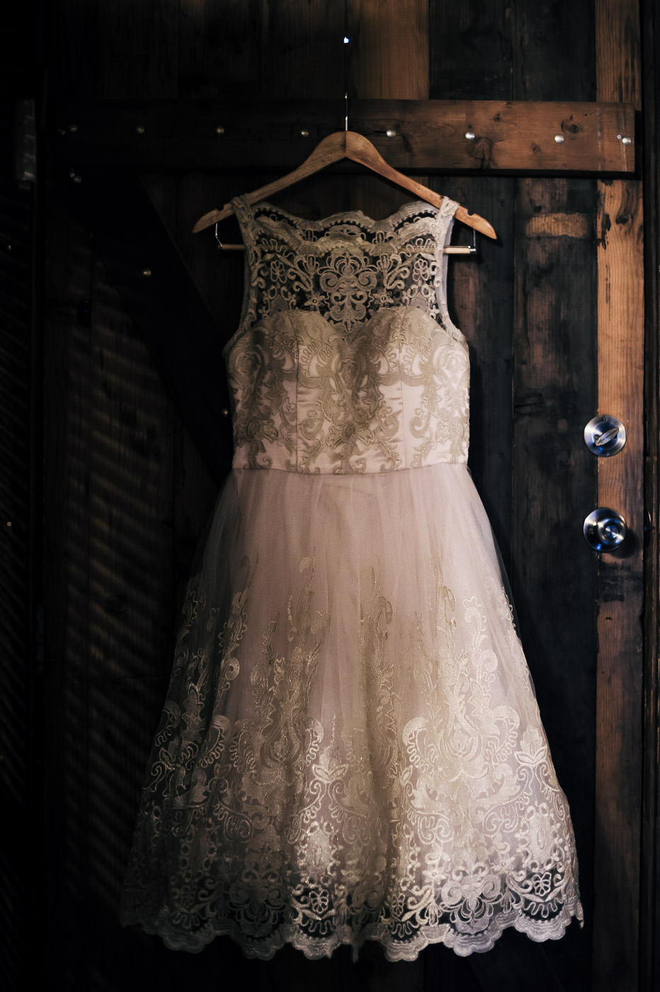 short lace wedding dress with lots of charming details hangs against an old wooden door