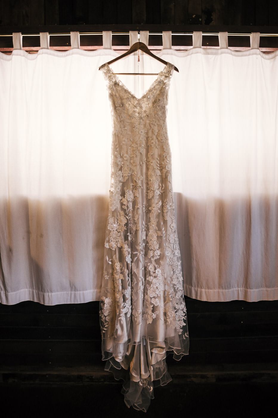 brides beautiful dress for the wedding ceremony backlit by window light as it hangs in the dressing room.