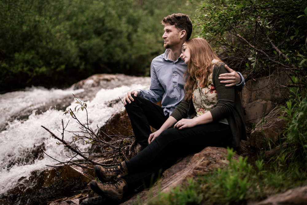 Couple sits close and enjoys a moment togeather by a rushing river in Sequoia National park  for their engagement