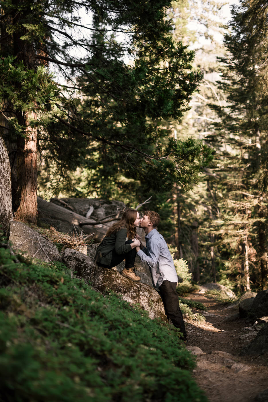 Couple kisses along the hiking trail at sunset in Sequoia National Park California for a romantic engagement