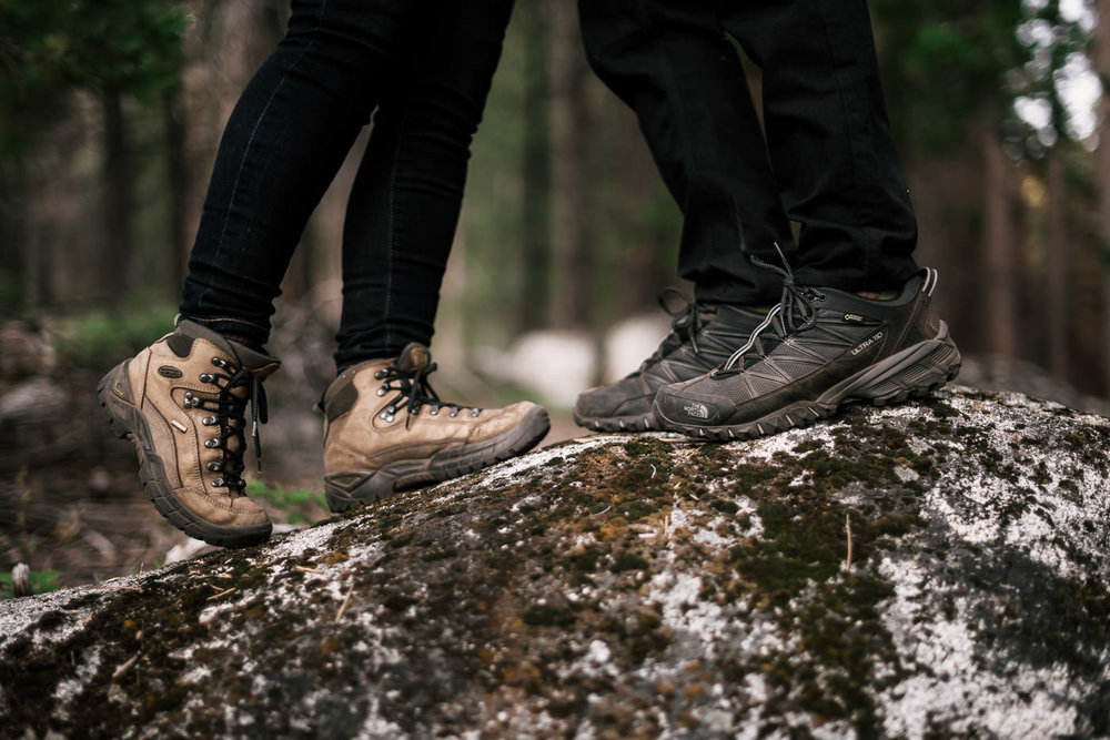 the hiking boots of two loverbirds sharing a kiss during their engagement session in seqouia national park