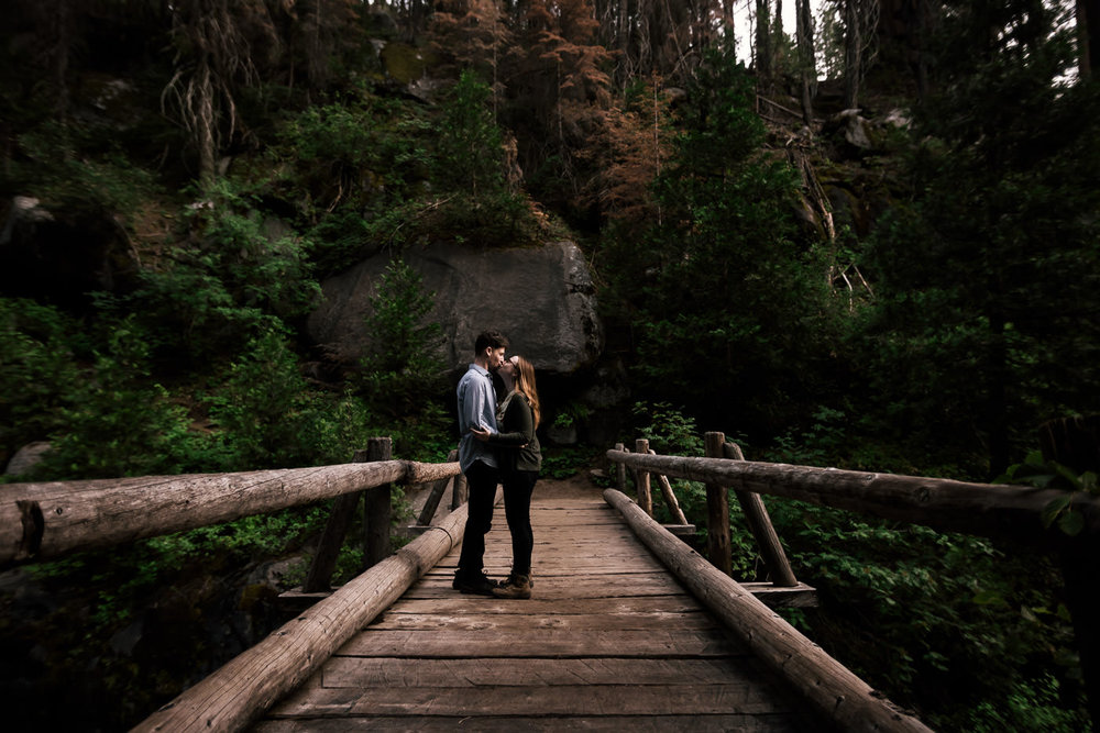 romantic kiss between a couple on an old wooden bridge during their intimate engagement session in seqouia national park