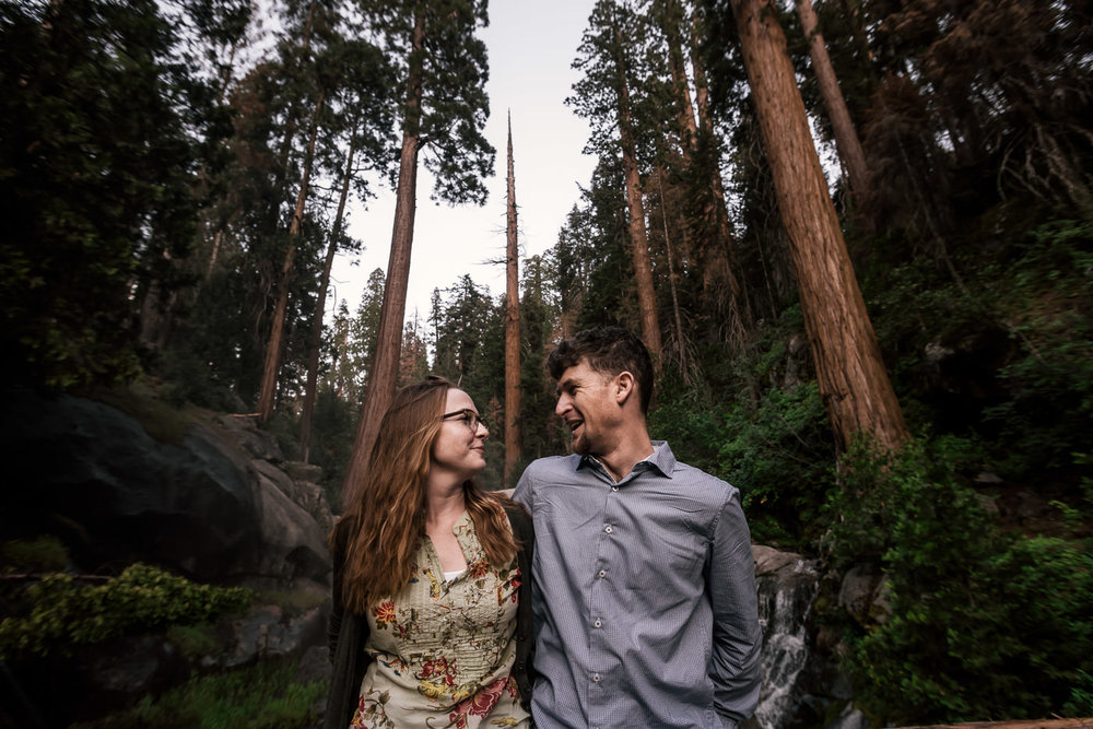 Towering Giant sequoia and a thundering waterfall surround this lovely couple on their engagement session in sequoia national park