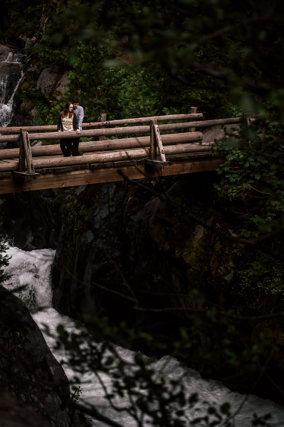 An old wooden bridge spanning the churning water of the river below makes the perfect setting for a romantic engagement photo in Sequoia National Park