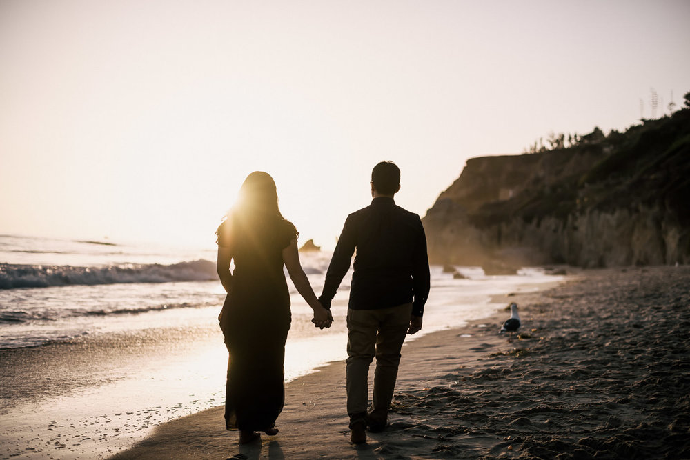 Silhouetted couple walks together with hands held tight down the picturesque beach of El Matador into the golden setting sun in Malibu. A romantic photo captured by their Wedding photographer.