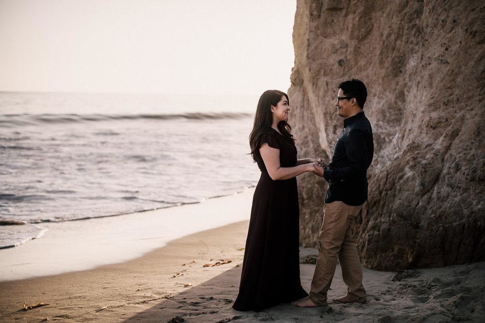 Pair of lovers holds hands on the beach and enjoys the sand in their toes during their El Matador beach Engagement.