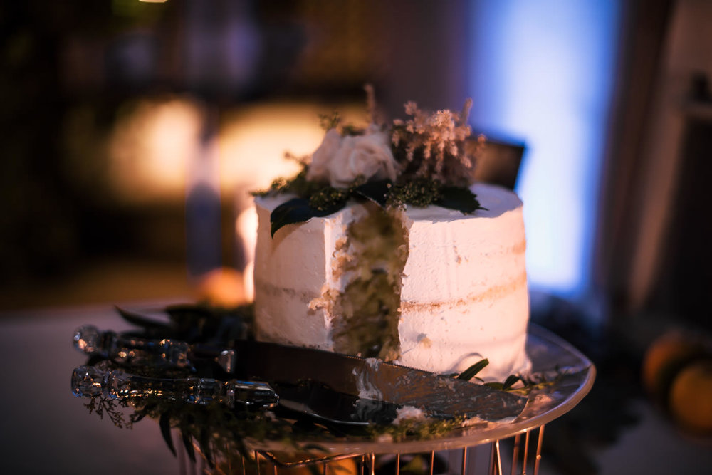 Beautiful and simple wedding cake cut by the bride and groom at their reception