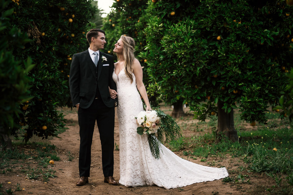 Gorgeous couple poses for their wedding photographer and create a romantic portrait in this stunning orange orchard in Temecula California.