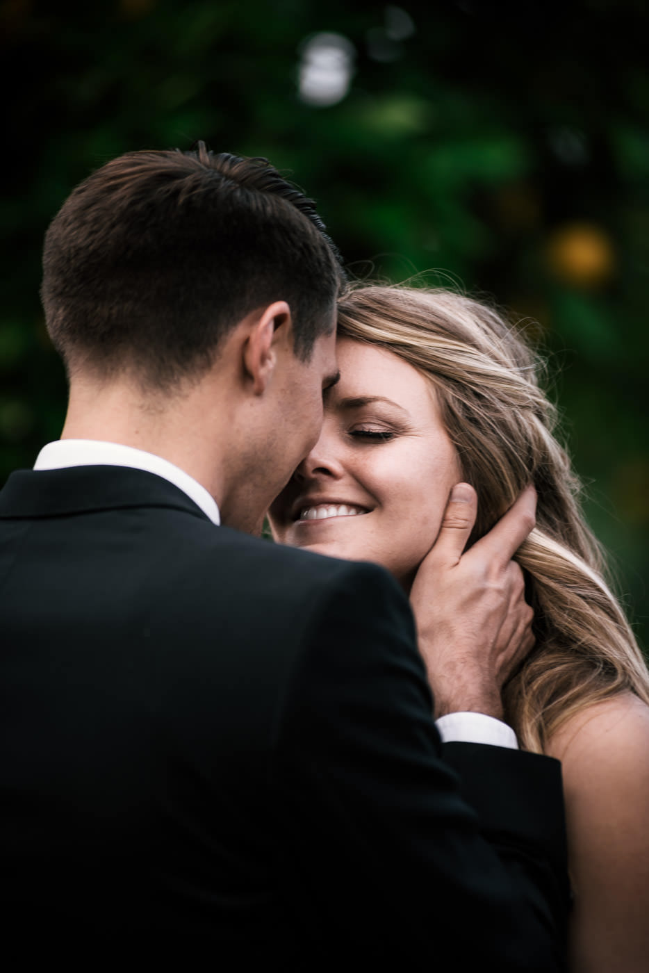Couple gets in close and doesnt hold back loving on each other in the orchard after their wedding in Temecula. The bride is all smiles as her new husband gently pulls her in for a kiss.