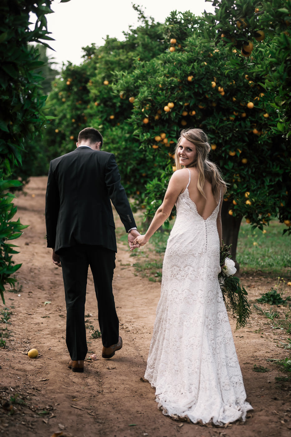 Groom leads his bride on a romantic walk through the orange orchards of Temecula California at their June wedding.