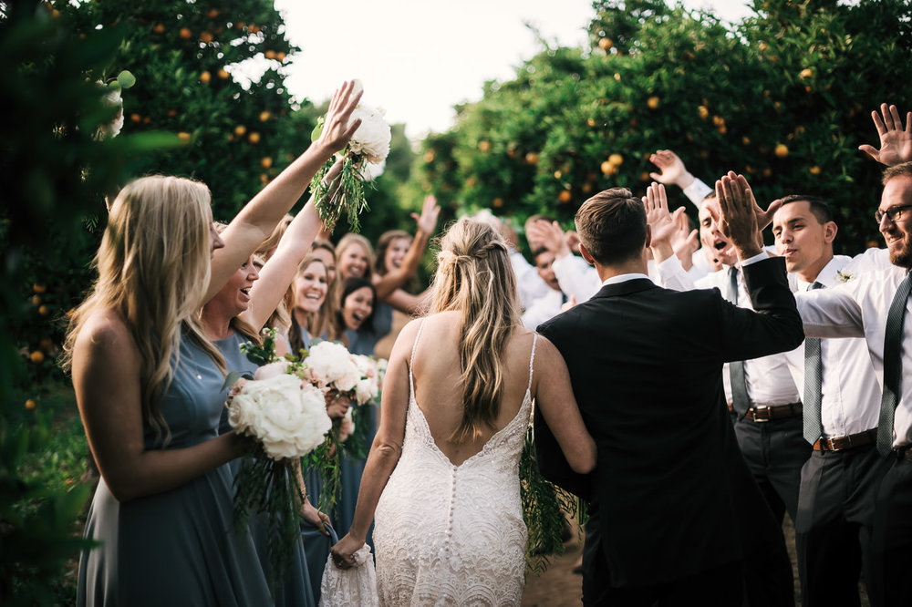 Groom high fives his friends as he walks his bride through an orange orchard in Temecula California after their wedding.