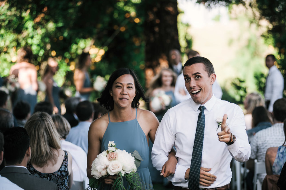 Groomsmen gives a thumbs up as he walks a happy bridesmaid down the asile after a emotional wedding in Temecula California