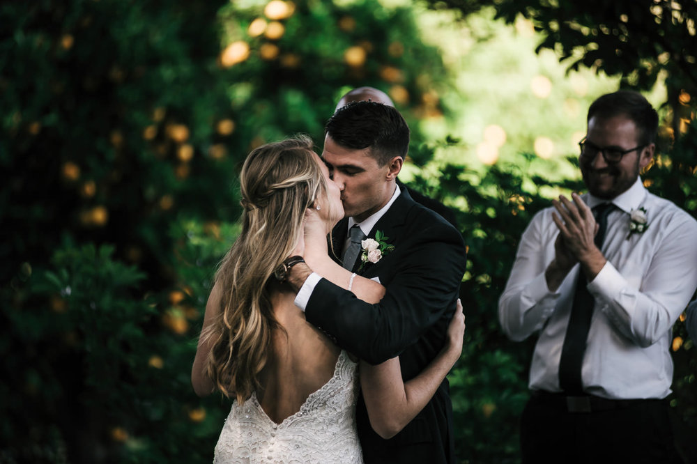 The orange orchard made for a perfect backdground fot this romantic first kiss at a Temecula wedding.