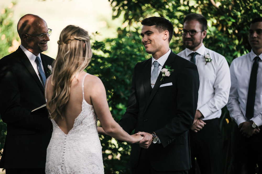 Couple looks at each other lovingly as the minister, who is also the father of the bride, begins the wedding ceremony at this touching Temecula wedding.