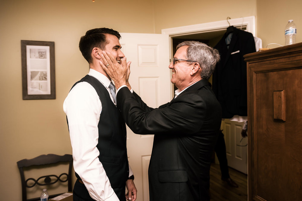 father lovingly grabs his sons face to congratulate him on his wedding in Temecula California