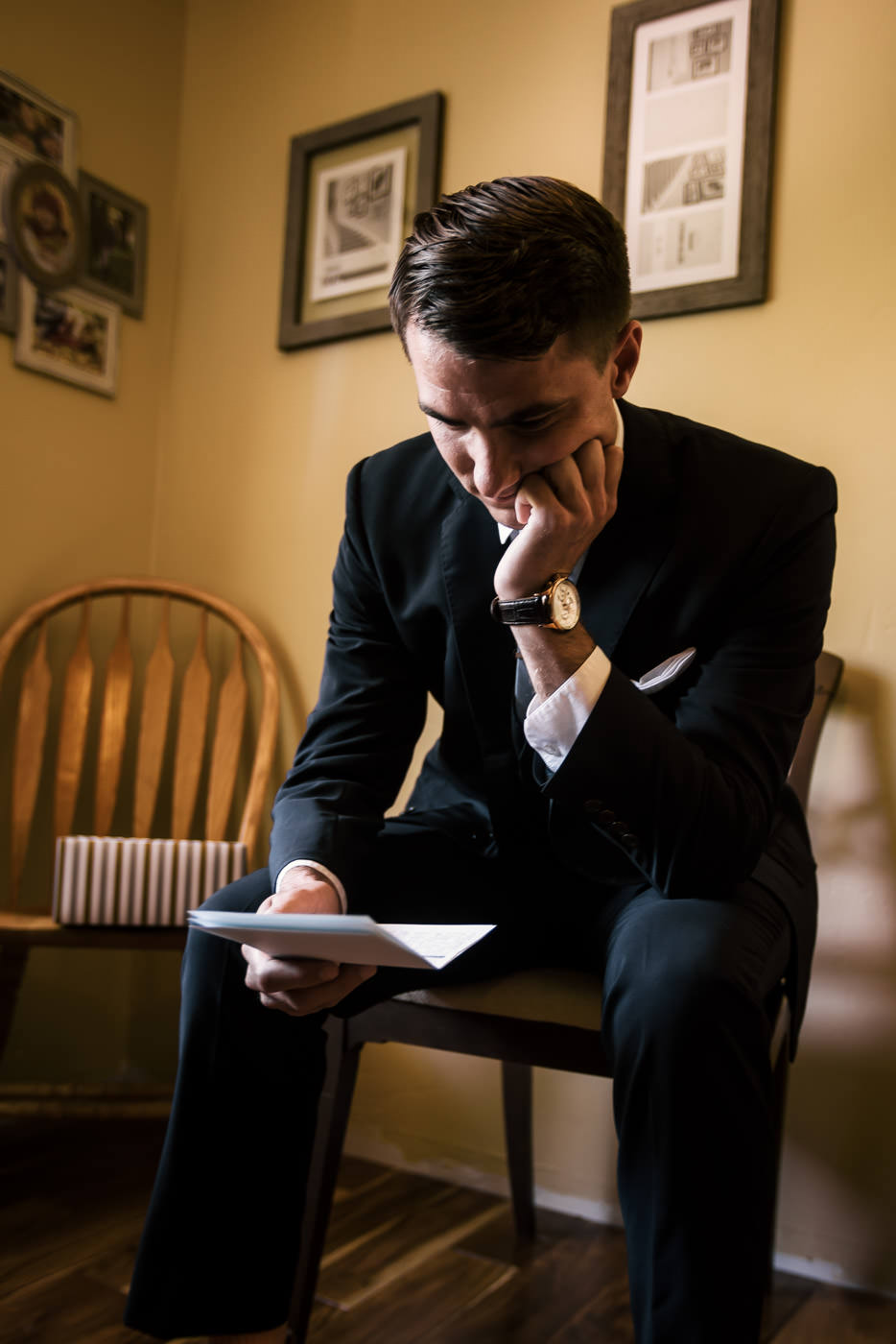Groom takes a seat on a wooden chair in his suite to read a touching love letter from his bride to be before their wedding in Temecula.