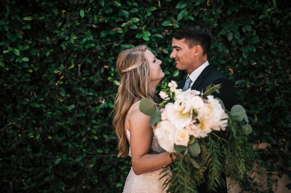 Couple has a romantic first look in fornt of a wall of ivy before the wedding ceremony at their temecula wedding.