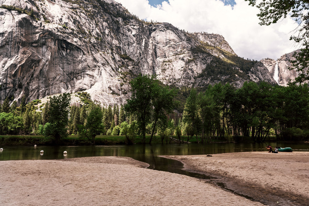 The sandy shores of Sentinel beach with the looming granite peaks of the Yosemite Valley in the background.