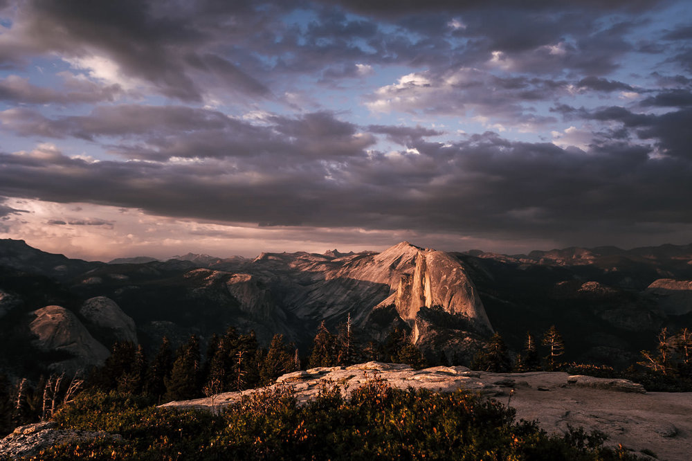 The majestic Half Dome at sunset under a cloudy sky. Photographed from Sentinel Dome, a perfect place for an intimate elopement ceremony.