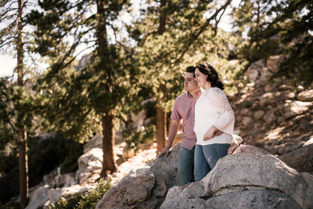 Lovers stand atop a mountain and look off into the distance during their engagement shoot.