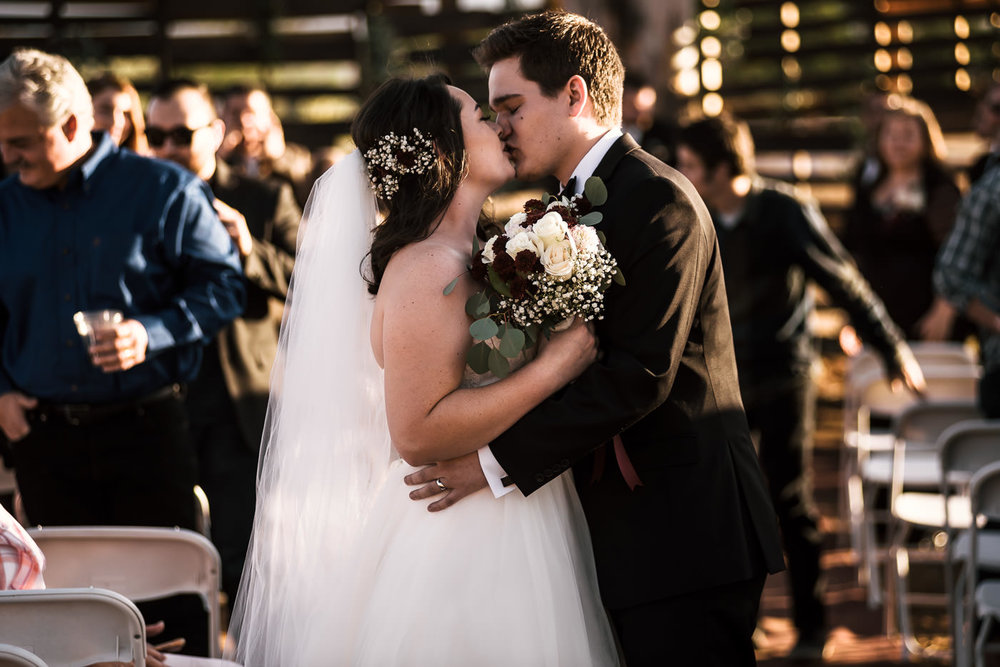 Newly weds kiss as they walk down the aisle at their Temecula Wine country wedding.