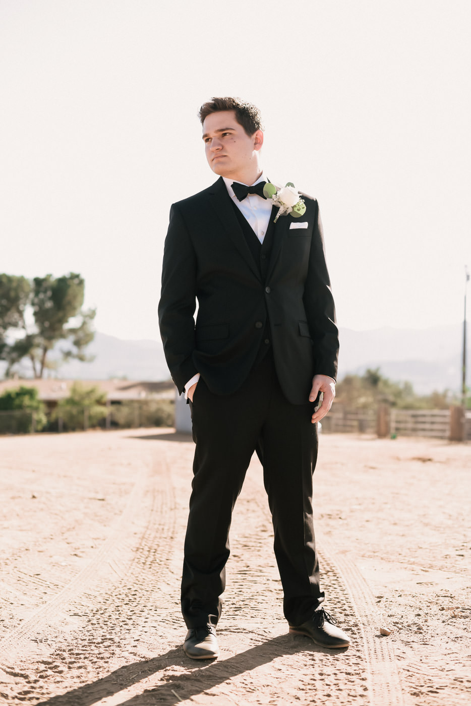 Handsome groom poses in his black suite in Temecula.