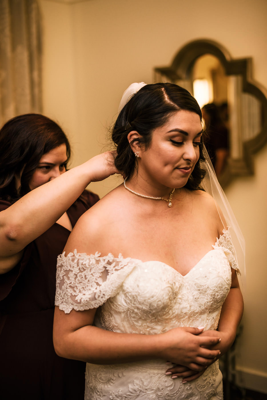Bridesmaid helps the bride put on her necklace.
