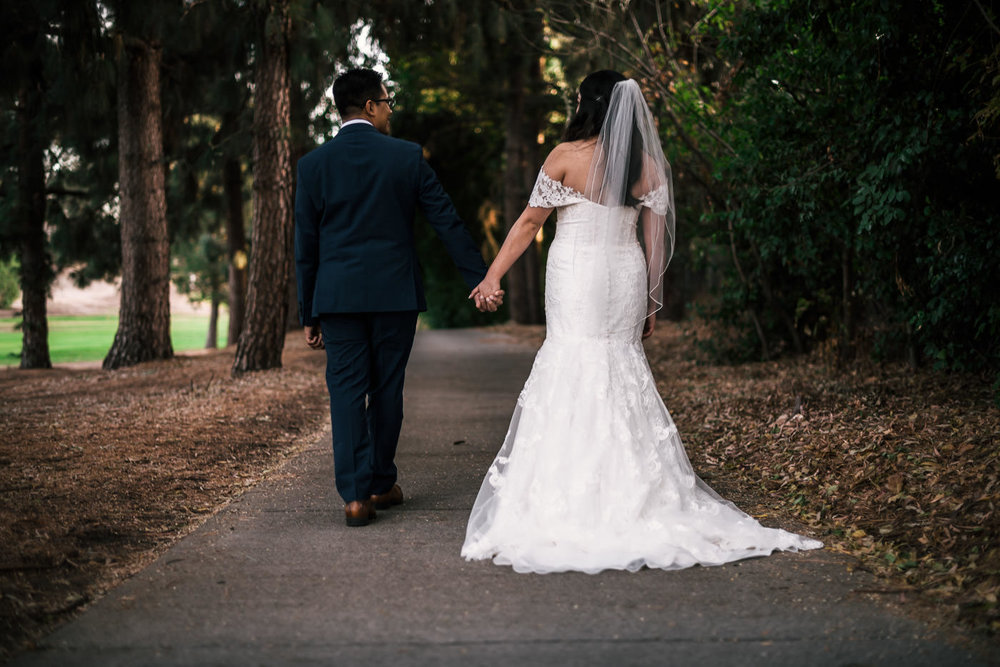 Newlyweds walk hand in hand down the beautiful paths of the Knollwood Country Club.