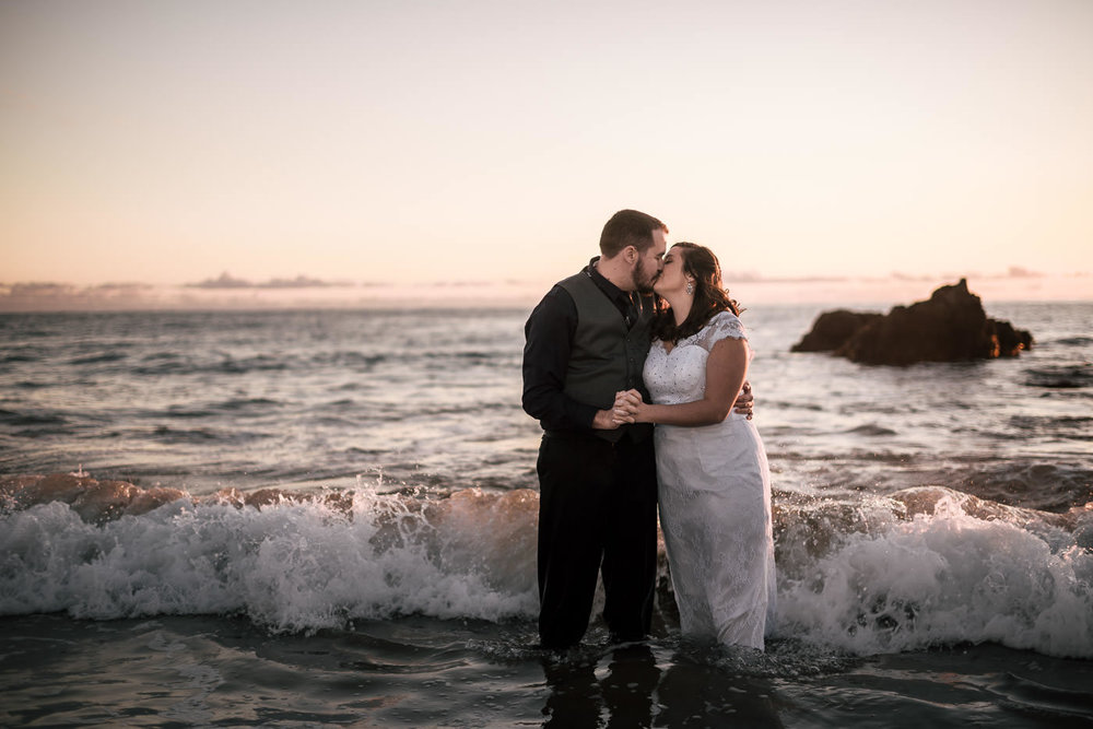 Newlyweds kiss at sunset as the waves crash around them in Laguna Beach.
