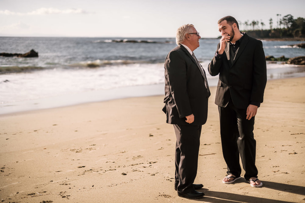 Groom talks with the minister on the sand at Laguna Beach.