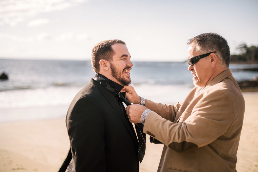 Father helps groom with his tie before the wedding at Laguna Beach.