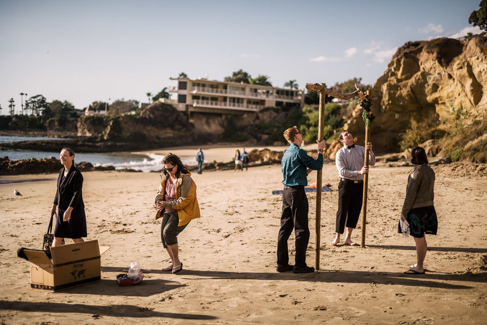 Family and friends help set up the driftwood altar for the ceremony at Laguna Beach.
