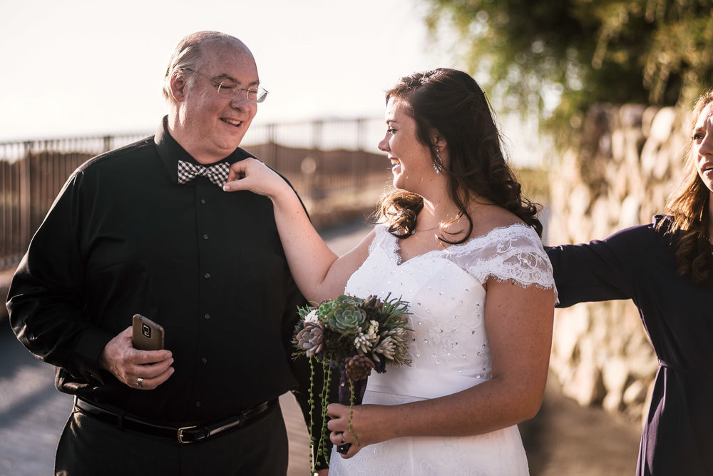 Bride straightens her fathers bowtie before he walks her down the aisle.