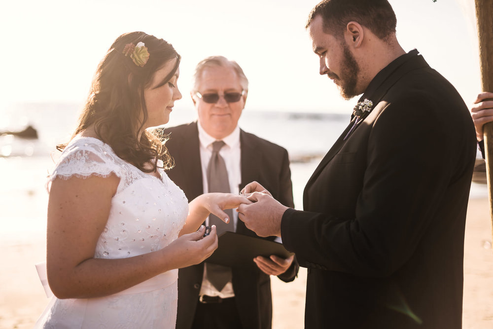 Couple exchanges wedding rings under the light of the setting sun on the sands of Laguna Beach.